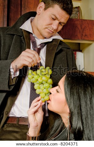 young couple eating grape, indoor - stock photo