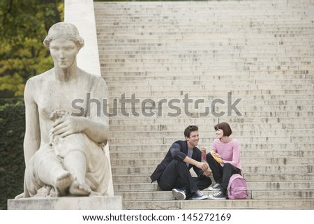 Young couple eating lunch while sitting on stairs - stock photo