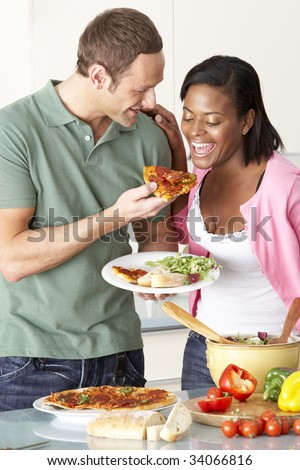 Young Couple Eating Meal In Kitchen - stock photo