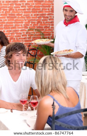 Young couple eating out in a pizzeria