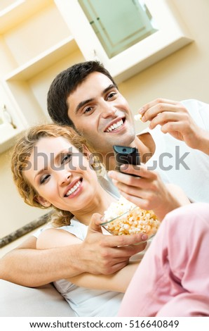 Young couple eating popcorn and watching TV together at home. Love, relations, romantic concept shoot.