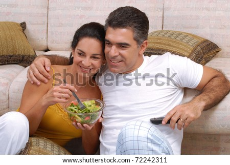 Young couple eating salad in a living room. - stock photo