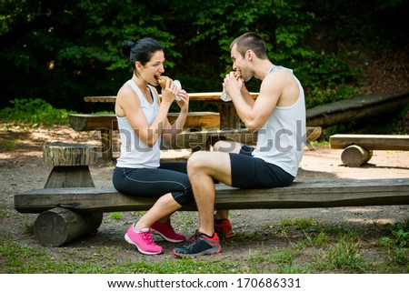 Young couple eating together after jogging outdoor in nature - stock photo