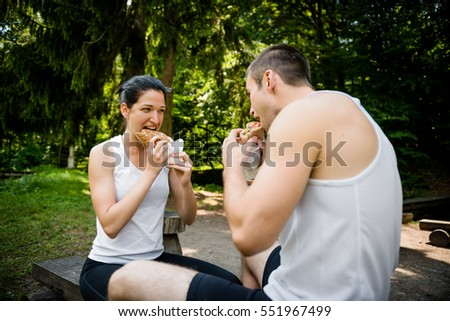 Young couple eating together after jogging outdoor in nature