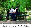 Young couple embrace on bench - stock photo