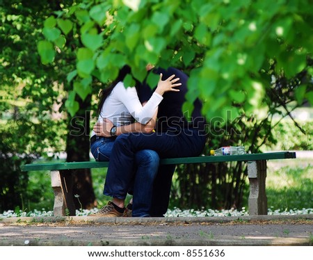 Young couple embrace on bench
