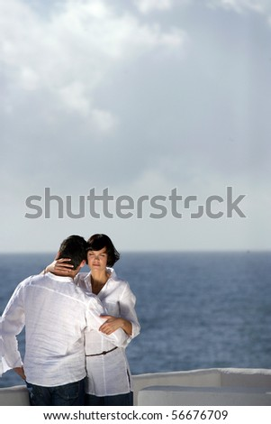 Young couple embraced face to the sea