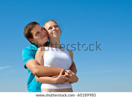 young couple embracing and looking in the sky - stock photo