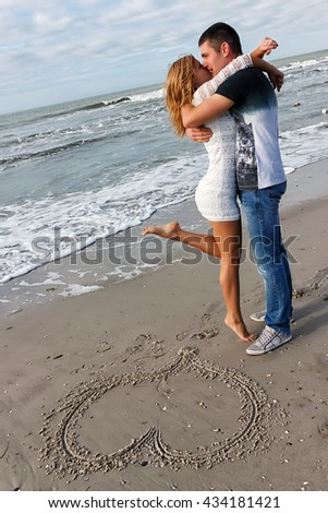 Young couple embracing by the sea or ocean. On the sand pattern in the form of heart. Figure symbolizes love and a happy married life. - stock photo
