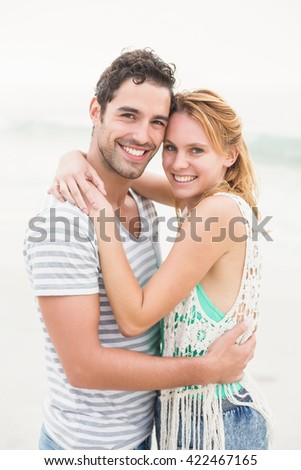 Young couple embracing each other on the beach on a sunny day - stock photo