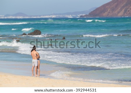 Young couple embracing, enjoying vacations on El Corralejo beach, famous holiday destination on Fuerteventura, Canary Islands, Spain. - stock photo