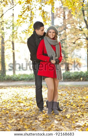 young couple embracing in autumn park, wearing fashionable clothes - stock photo