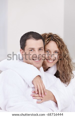 Young couple embracing in robes - stock photo