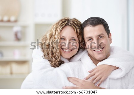 Young couple embracing in robes at home - stock photo