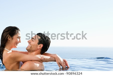 Young couple embracing in the pool - stock photo