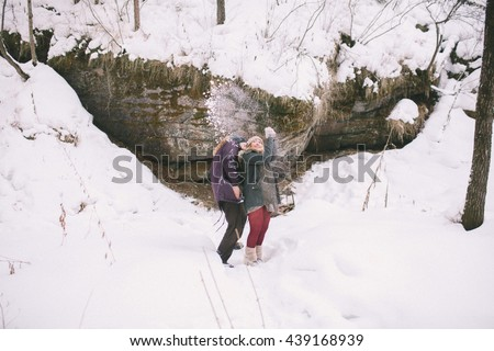 Young Couple Embracing in Winter Forest. Winter Vacations. Weekend Getaway.  - stock photo