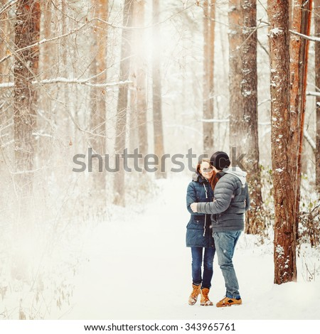 Young Couple Embracing in Winter Forest. Winter Vacations. Weekend Getaway. Space for Text. Natural Colors, Selective Focus. Instagram color effect. - stock photo