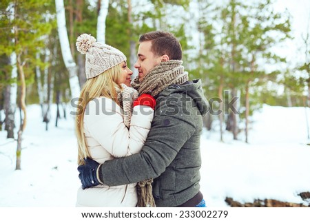 Young couple embracing in winter park - stock photo