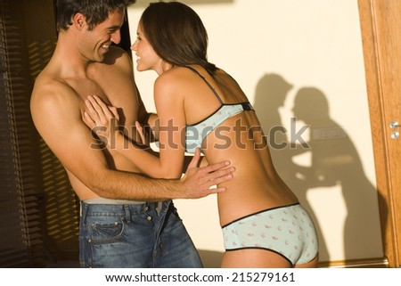 Young couple embracing indoors, laughing - stock photo