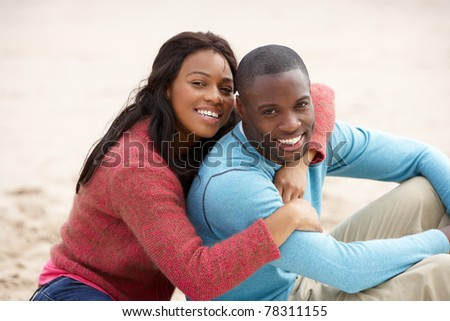 Young couple Embracing on beach - stock photo