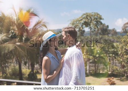 Young Couple Embracing On Summer Terrace Or Balcony Over Beautiful Tropical Landscape Background