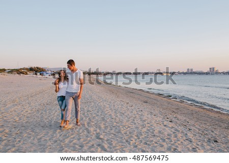 young couple embracing while walking along the beach