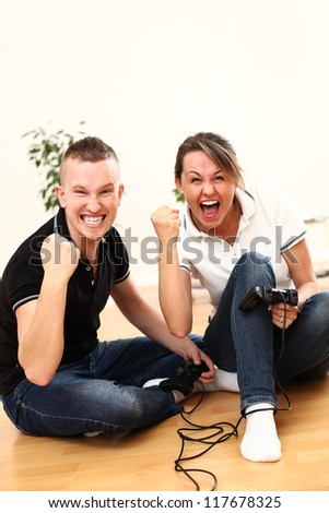 Young couple emotionally with passion play video games at home on the floor - stock photo
