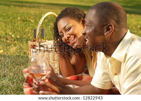 Young couple enjoying a beautiful summer day outside with a wine picnic - stock photo
