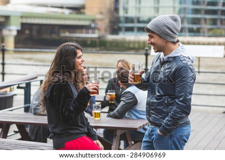 Young couple enjoying a beer at pub in London with more people on background. Outdoor scene, winter season, love and friendship concepts. - stock photo
