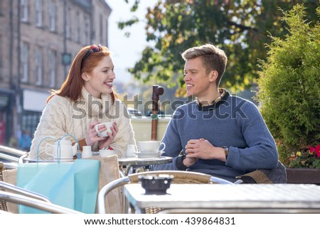 Young couple enjoying a cup of tea at a cafe together. they are sitting outdoors in the city.