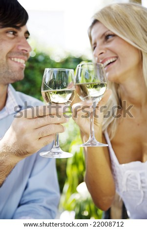 young couple enjoying a glass of white wine in the garden on a summer day - stock photo