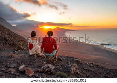 Young couple enjoying beautiful sunset sitting together on the mountain with great view on Cofete coastline on Fuerteventura island - stock photo