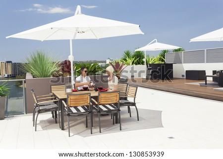 Young couple enjoying breakfast on modern balcony - stock photo