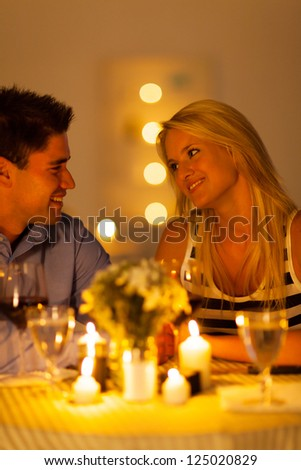 young couple enjoying candlelight dinner in a restaurant - stock photo