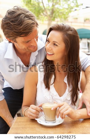 Young Couple Enjoying Coffee And Cake In Cafe
