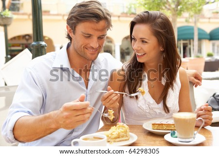 Young Couple Enjoying Coffee And Cake In Cafe - stock photo