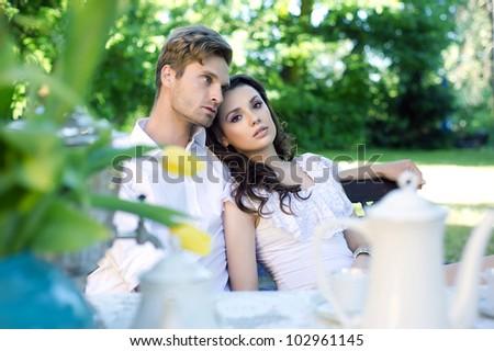 Young couple enjoying coffee in the garden - stock photo