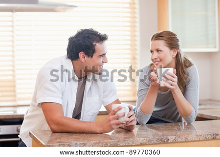 Young couple enjoying coffee in the kitchen together - stock photo