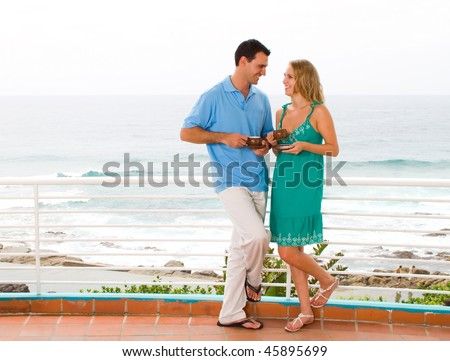 young couple enjoying coffee on balcony with beautiful ocean view behind - stock photo