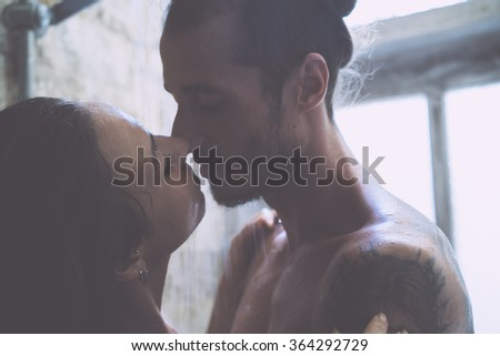 young couple enjoying each other in the shower - stock photo