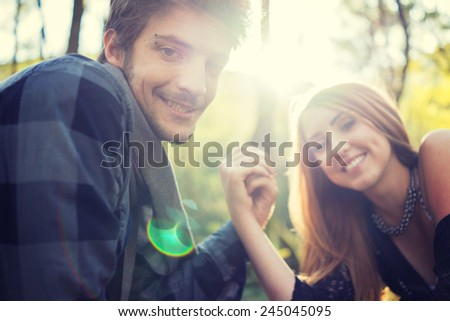 Young couple enjoying in beautiful park at river before sunset - stock photo