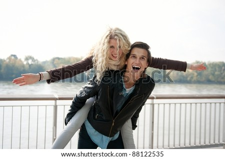 Young couple enjoying life together outdoor - man holding woman who pretends to fly - stock photo