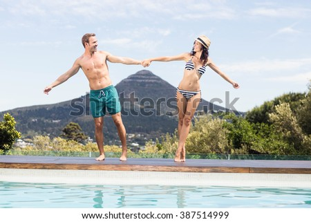 Young couple enjoying near pool side on a sunny day - stock photo