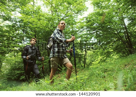 Young couple enjoying nordic walking in a forest - stock photo