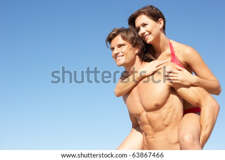 Young Couple Enjoying Piggyback On Beach Holiday