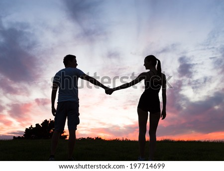 Young couple enjoying sunset in the meadow. - stock photo