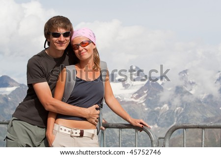 Young couple enjoying the sun high in the mountains - stock photo