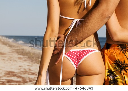 Young couple enjoying themselves on the sea shore - stock photo