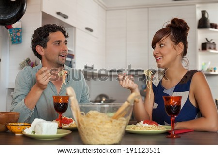 Young couple enjoying wine and spagetti  - stock photo