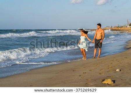 Young couple enjoys walking on a hazy beach at dusk. - stock photo
